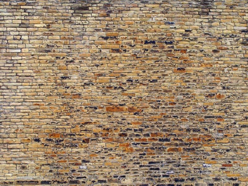 Bruine en gele openluchtsteenmuur met vele ongelijke ruwe bakstenen en geweven oppervlakte stock afbeeldingen