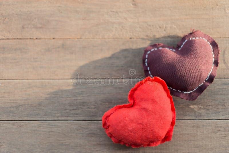 Bruine en rode harthoofdkussens op houten lijst met zonneschijn stock afbeeldingen