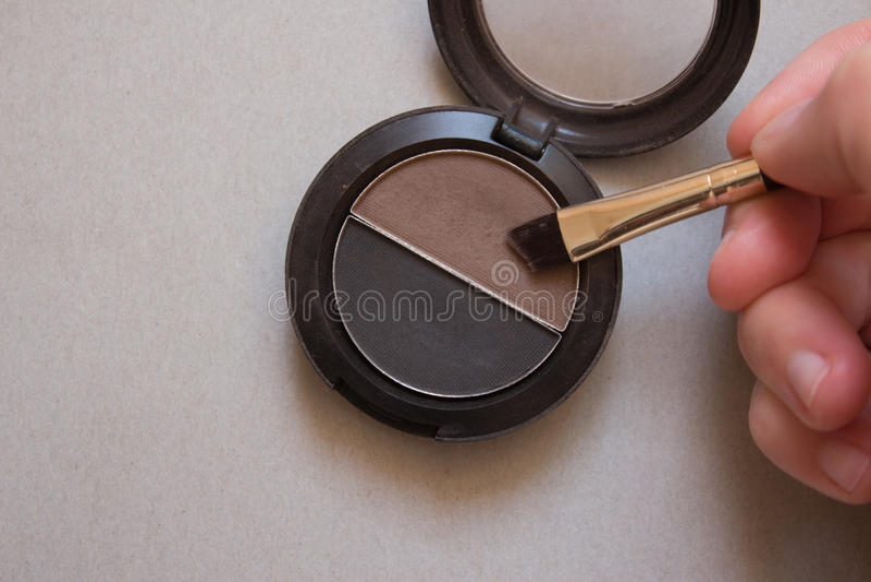 Bruine en zwarte schaduwen voor brows, borstel en vrouwelijke hand royalty-vrije stock afbeelding