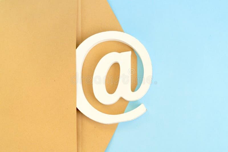 Bruine envelop met e-mail@-teken op blauwe achtergrond stock foto's