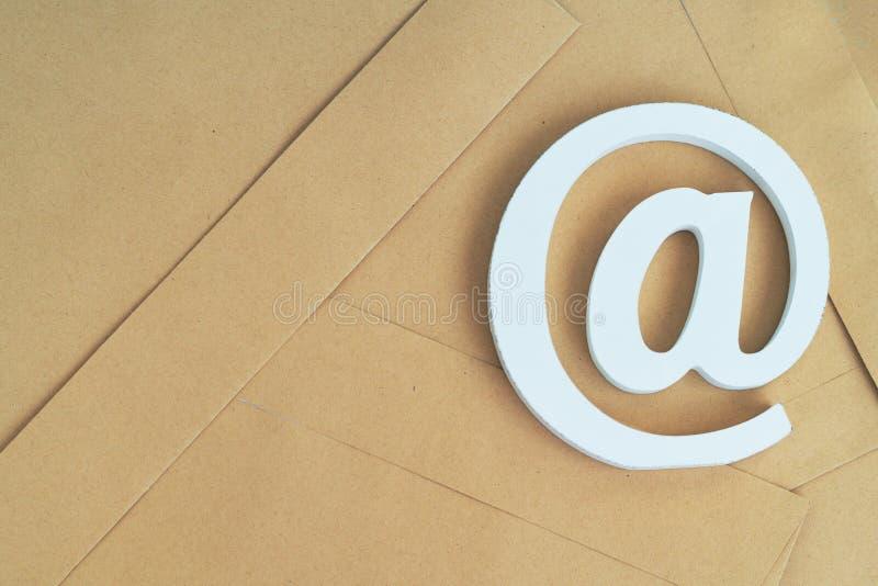 Bruine envelop met e-mail@-teken op blauwe achtergrond royalty-vrije stock foto's