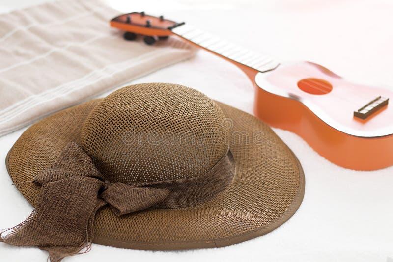 Bruine floopy hoed met lint, weinig gitaarstuk speelgoed en handdoek backgr stock fotografie