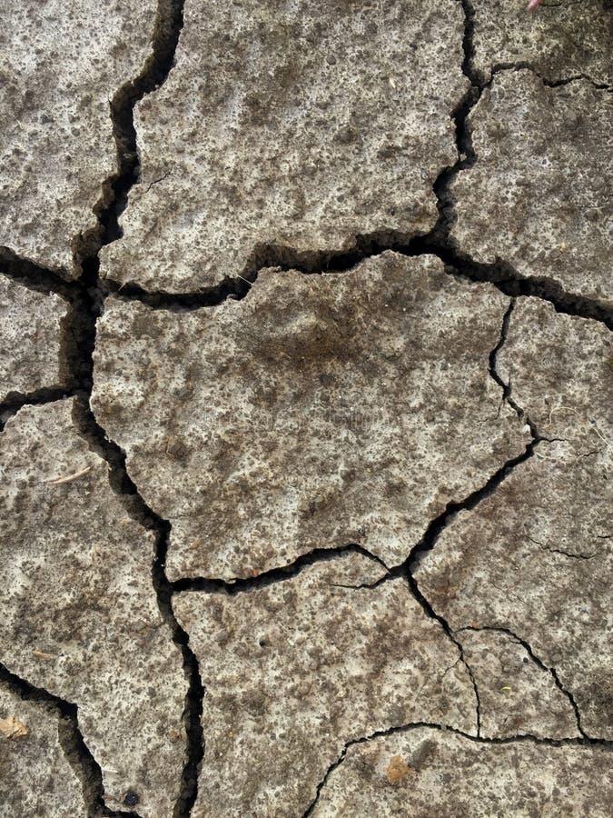 Bruine Gebarsten grond als achtergrond, Barsten op de oppervlakte van de aarde stock afbeeldingen