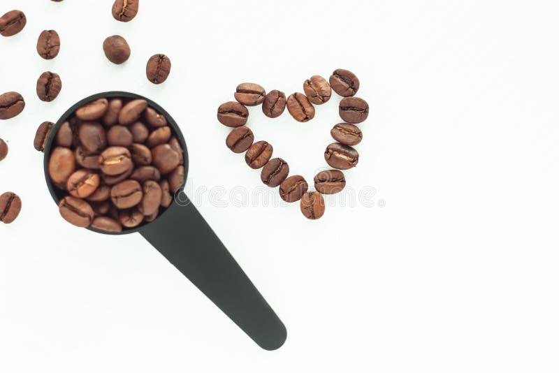 Bruine geroosterde koffiebonen in een zwarte metende lepel op een witte geïsoleerde achtergrond royalty-vrije stock afbeelding