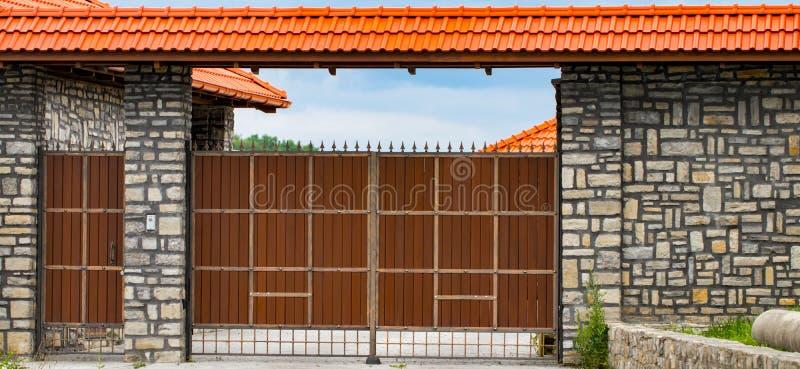 Bruine gesmede automatische poorten in het plattelandshuisje royalty-vrije stock afbeelding