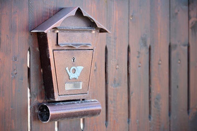 Bruine geweven metaalpostbox met een pictogram die van de posthoorn op een houten omheining hangen Concept brievenbus en postleve stock afbeeldingen