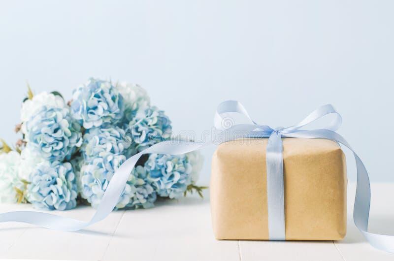 Bruine giftdoos met blauwe van de lintboog en Hydrangea hortensia bloemen stock foto's