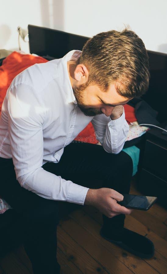 Bruine haar Turkse kerel elegant in witte overhemdszitting in zijn bed die zijn berichten van de smartphonelezing controleren royalty-vrije stock afbeelding