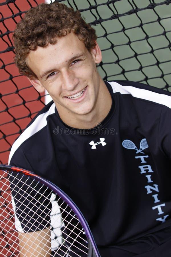 Bruine haired jonge mens die met tennisracket glimlacht stock afbeelding