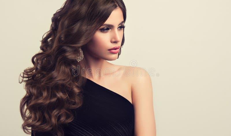 Bruine haired vrouw met omvangrijk, glanzend en krullend kapsel Kroeshaar stock afbeelding