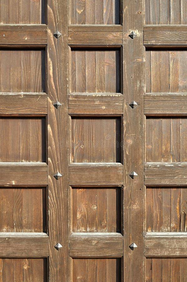 Bruine houten deur met oude metaalklinknagels - retro tonen geweven achtergrond stock afbeeldingen