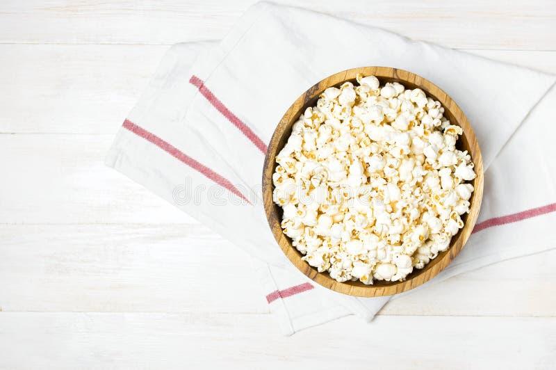 Bruine houten kom met heerlijke traditionele popcorn op een lichte houten achtergrond Hoogste mening van een lichte maaltijdachte stock foto