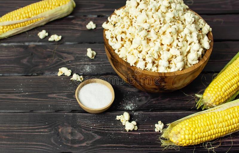 Bruine houten kom met heerlijke traditionele popcorn, vers graan en een lepel op een donkere houten achtergrond Hoogste mening va stock fotografie