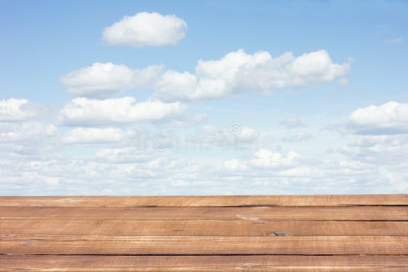 Bruine houten lijst aangaande een achtergrond van wolken stock afbeeldingen