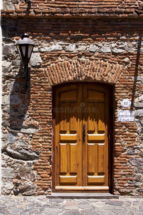 Bruine houten oude deur en een straatlantaarn stock fotografie