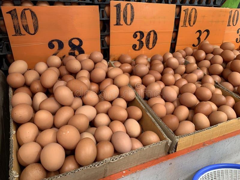 Bruine kippeneieren in kartondoos het verkopen in de markt stock foto's