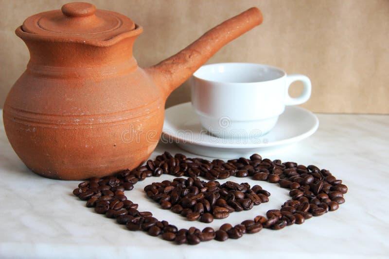 bruine klei Turk voor het koken van Arabische koffie, witte Kop en schotel en geroosterde koffiebonen in de vorm van een hart royalty-vrije stock foto