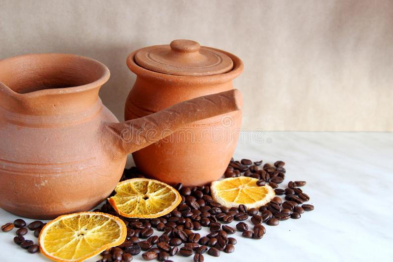 Bruine kleischotels De kruik van Turk en van de melk, van kleischotels wordt gemaakt, heel wat geroosterde koffieboon en droge si royalty-vrije stock fotografie
