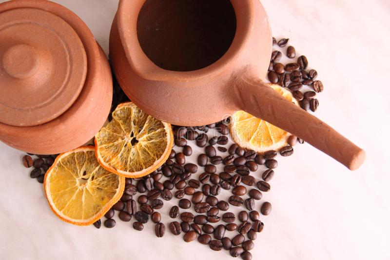 bruine kleischotels, kruik met handvat voor koffie en kruikmelk, heel wat geroosterde koffiebonen en droge sinaasappelen op de li royalty-vrije stock afbeeldingen