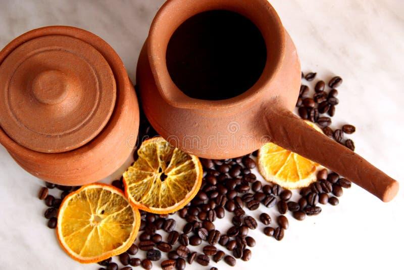 Bruine kleischotels, kruik met handvat voor koffie en kruikmelk, heel wat geroosterde koffiebonen en droge sinaasappelen op de li royalty-vrije stock fotografie