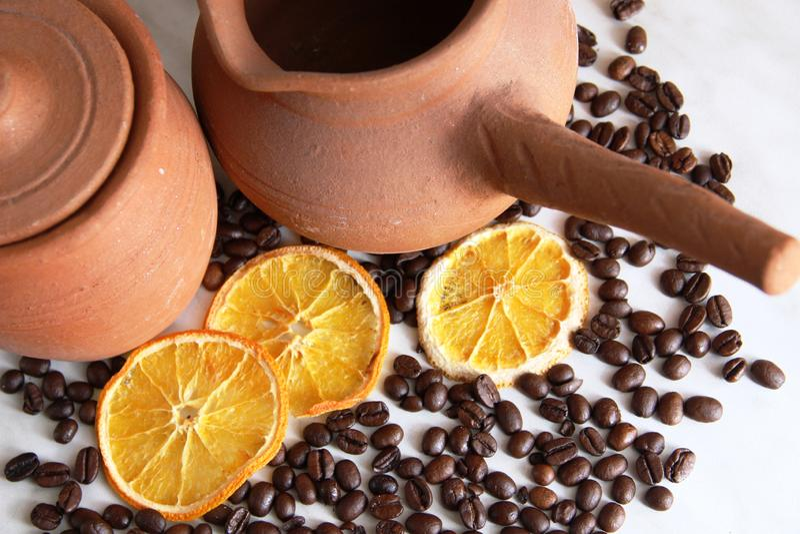 Bruine kleischotels, kruik met handvat voor koffie en kruikmelk, heel wat geroosterde koffiebonen en droge sinaasappelen op het g stock afbeeldingen