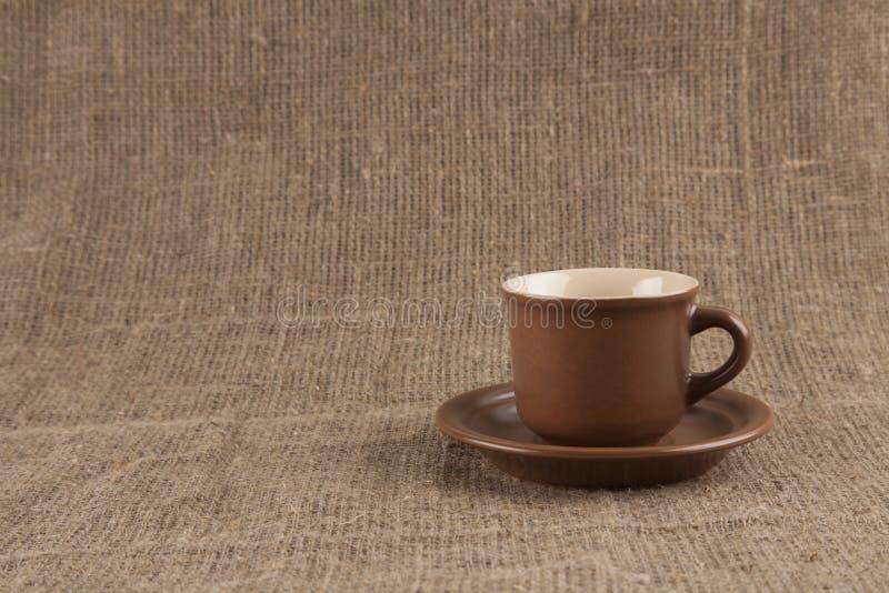 Bruine koffiekop op jute royalty-vrije stock foto's