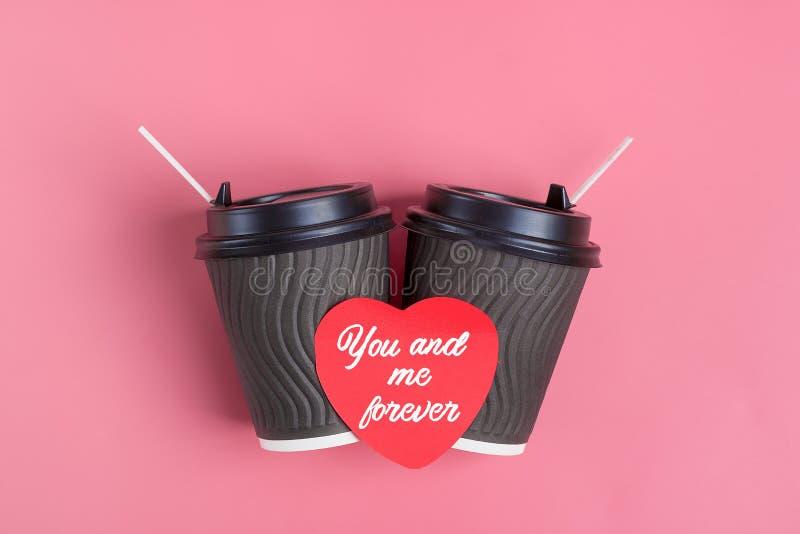Bruine koffiekoppen, rode hart-vormige sticker op roze achtergrond stock foto's