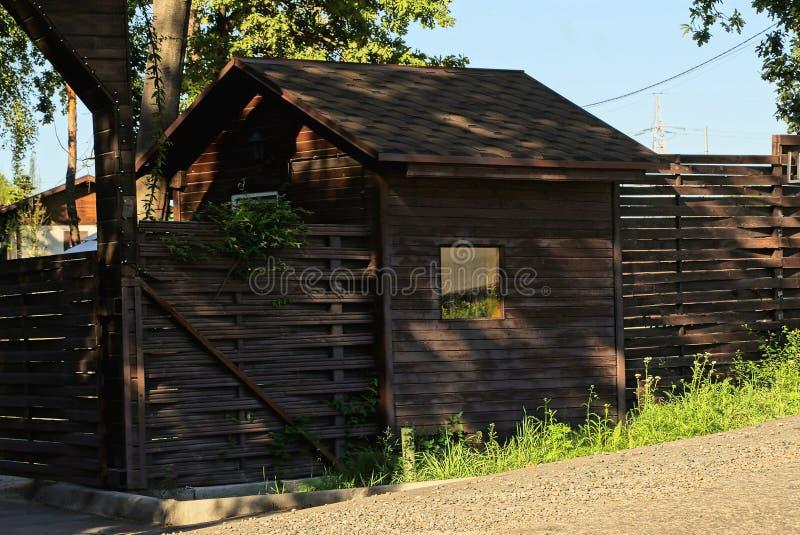 Bruine landelijke houten omheining en loods met een buiten venster stock afbeelding