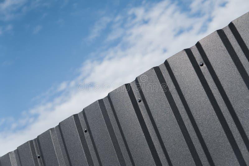 Bruine metaalplaat tegen blauwe bewolkte hemel Het opruimen Naadloze oppervlakte van gegalvaniseerd staal De industriële bouw gem stock foto