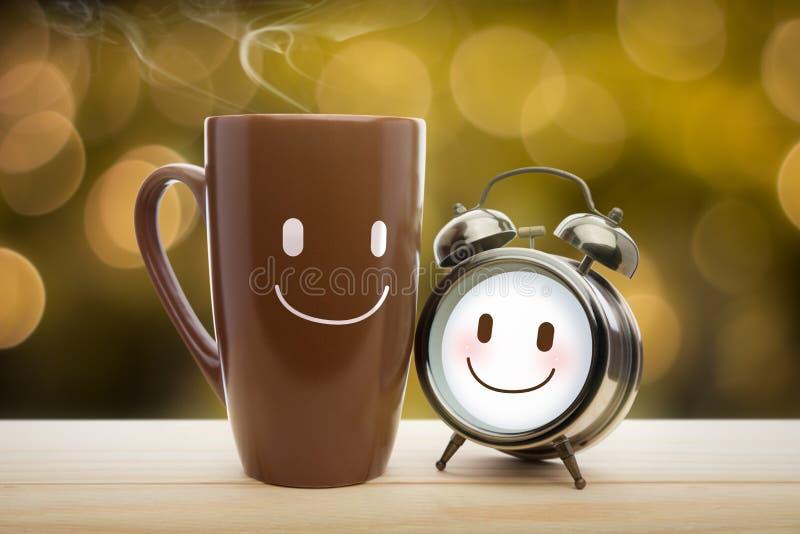 Bruine mok en wekker met een gelukkige glimlach stock foto
