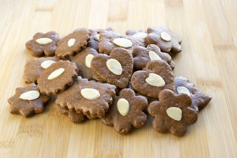 Bruine moravian donkere peperkoeken met gesneden amandelen op houten lijst, Kerstmiskoekjes stock foto