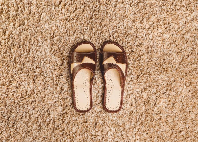 Bruine pantoffels op het tapijt stock foto