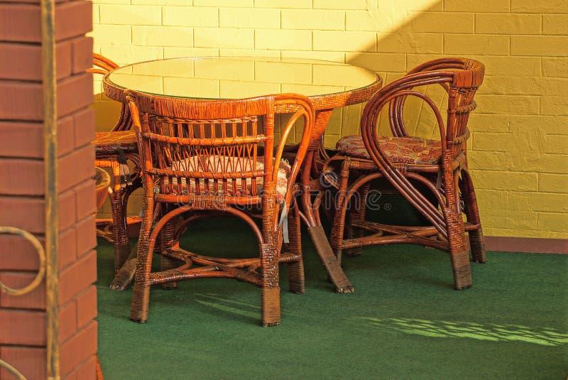 Bruine rieten stoelen en een glasrondetafel stock fotografie