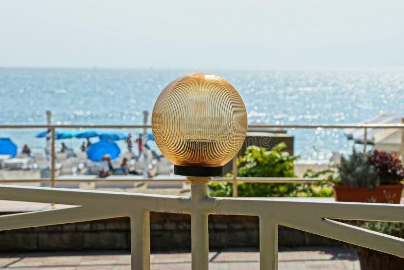 Bruine ronde lantaarn op een grijze metaalomheining tegen de achtergrond van het overzees en de hemel stock foto's