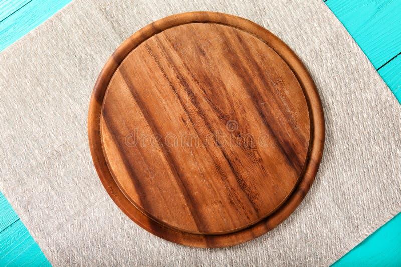 Bruine ronde pizza scherpe raad voor voedsel op grijs linnenservet Blauwe houten achtergrond in het restaurant De ruimte van het  stock foto
