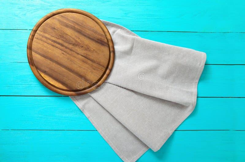 Bruine ronde pizza scherpe raad voor voedsel op grijs linnenservet Blauwe houten achtergrond in het restaurant De ruimte van het  royalty-vrije stock afbeeldingen