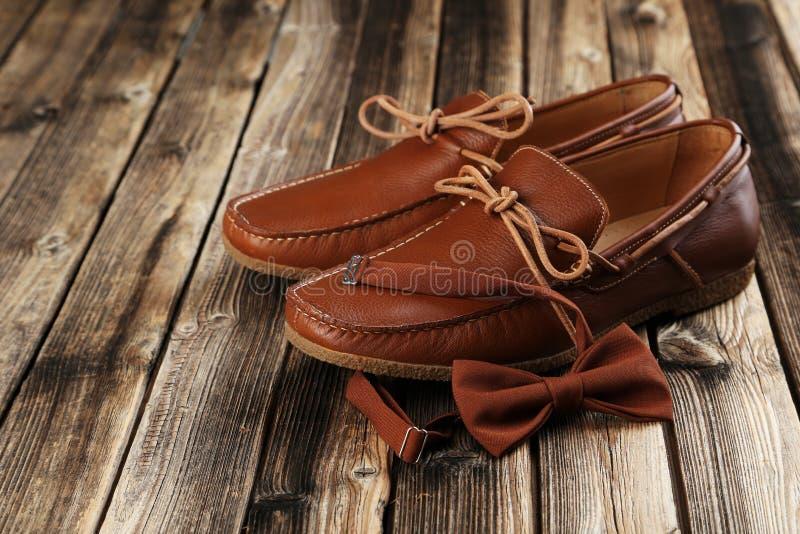 Bruine schoenen met vlinderdas stock afbeelding