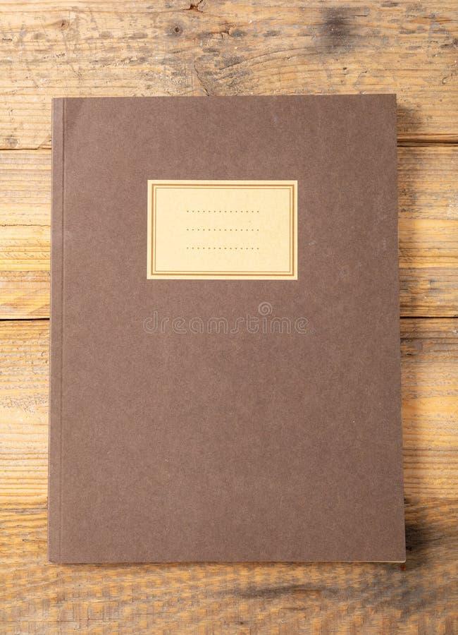 Bruine schoolnotitieboekje of agenda, ouderwets, op houten bureau, leeg etiket, ruimte voor tekst, hoogste mening stock fotografie