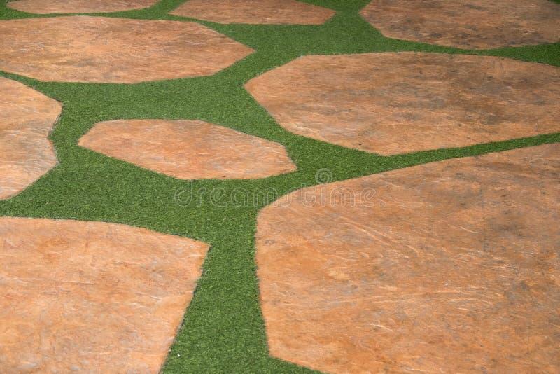 Bruine steen en de kunstmatige weg van het grasgras royalty-vrije stock afbeelding