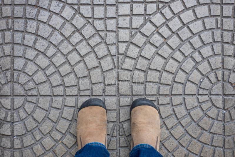 Bruine suèdeschoenen die zich op betegelde vloer bevinden royalty-vrije stock afbeeldingen