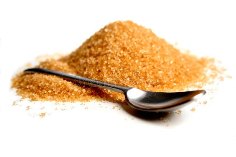 Bruine suiker en lepel op witte achtergrond stock afbeelding
