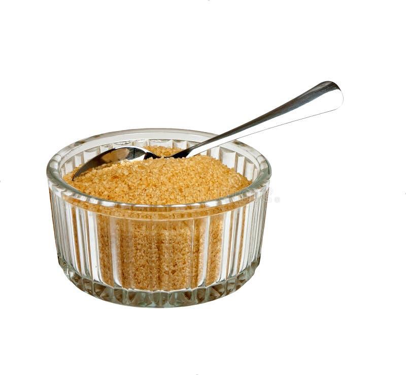 Bruine suiker in kom met geïsoleerde lepel, stock afbeelding