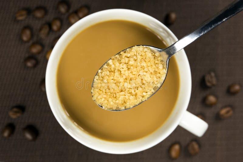 Bruine suiker op een lepel en een kop van koffie stock foto