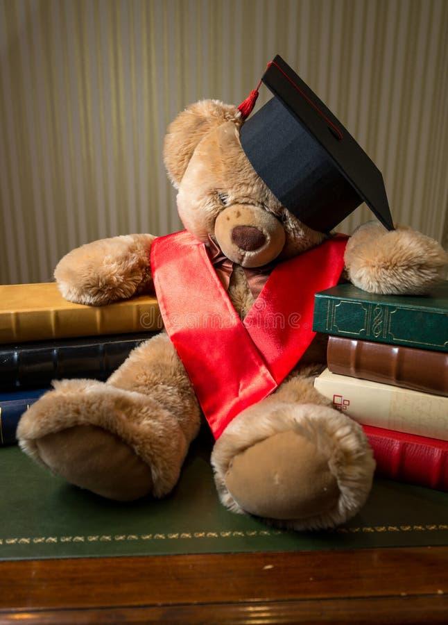 Bruine teddybeer die graduatie GLB dragen die op boeken leunen stock foto