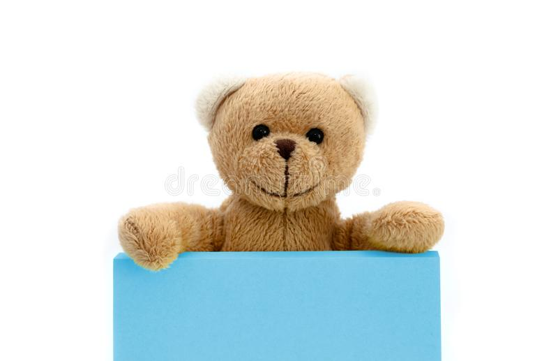 Bruine teddybeerholding met de twee handen een nota in pastelkleur blauwe kleur met lege ruimte voor tekstbericht stock foto