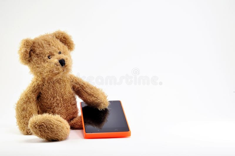 Bruine Teddybeerstuk speelgoed en celtelefoon met oranje lichaam royalty-vrije stock afbeelding