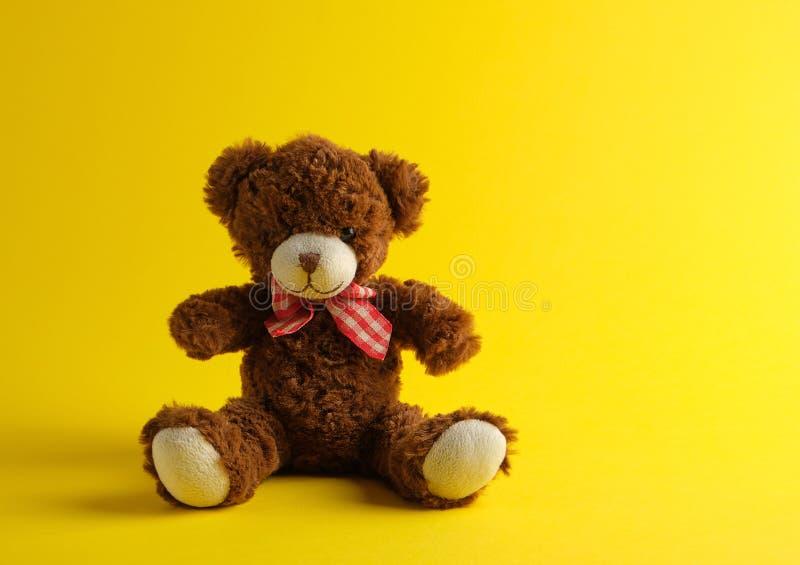 bruine teddybeerzitting op een gele achtergrond royalty-vrije stock afbeeldingen