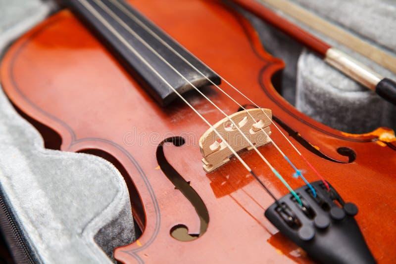Bruine uitstekende viool met boog die in een geval liggen royalty-vrije stock afbeelding