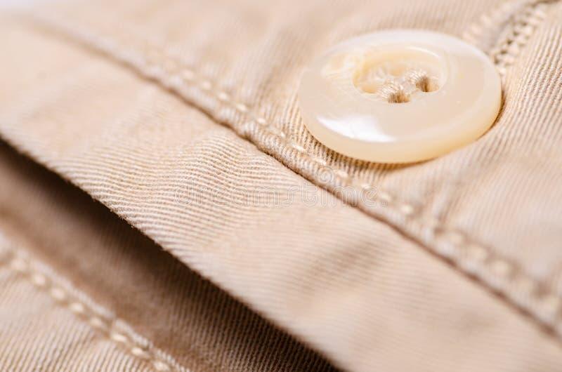 Bruine van de het textielproducttextuur van de jeansstof de knoopmacro stock afbeelding