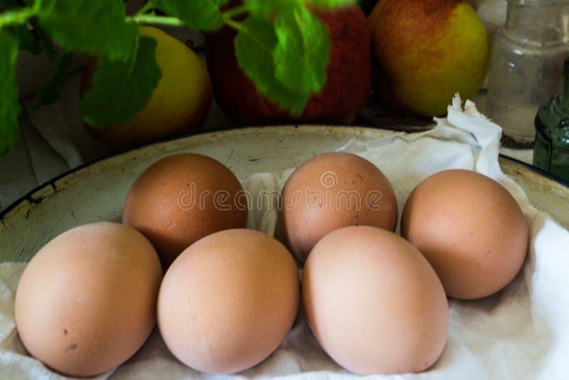 Bruine verse eieren op uitstekende emailplaat met verse munt en appelen op achtergrond stock afbeeldingen